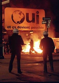A fire burns under a Oui sign.