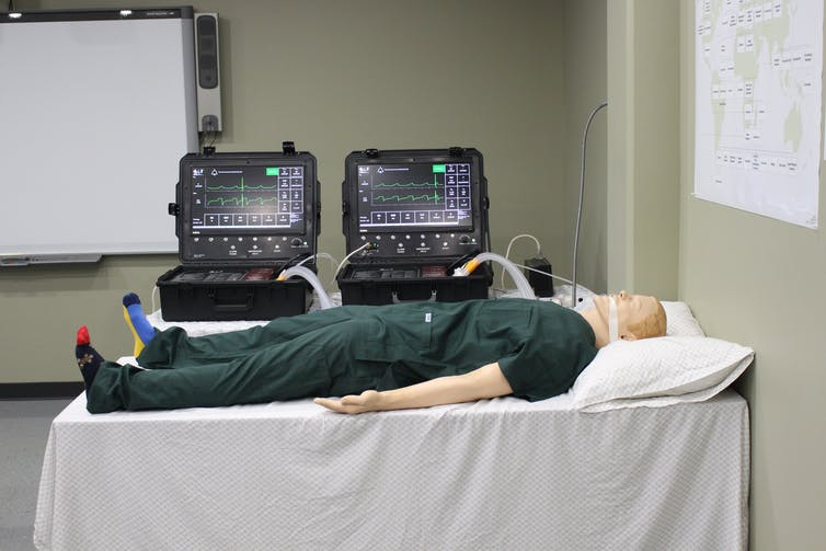 A medical dummy lying on a table with two ventilators behind it.