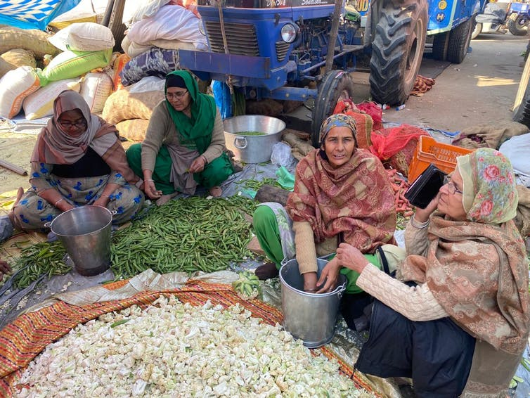 Four women are seen seated on the ground sorting through vegetables.