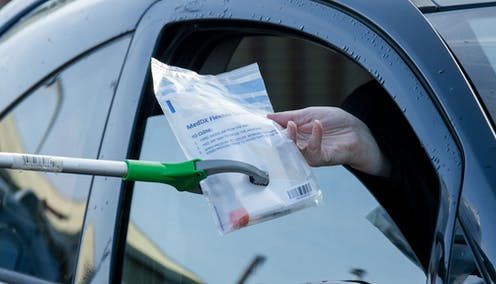 A person receiving a COVID testing kit through their car window