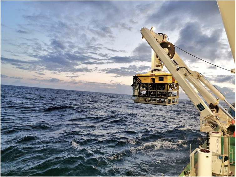 Some yellow equipment lowered from a crane into the sea