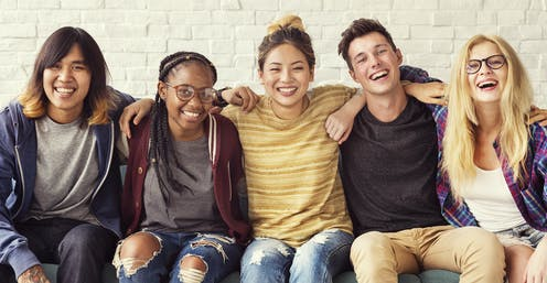Group of students smiling with arms round eachother