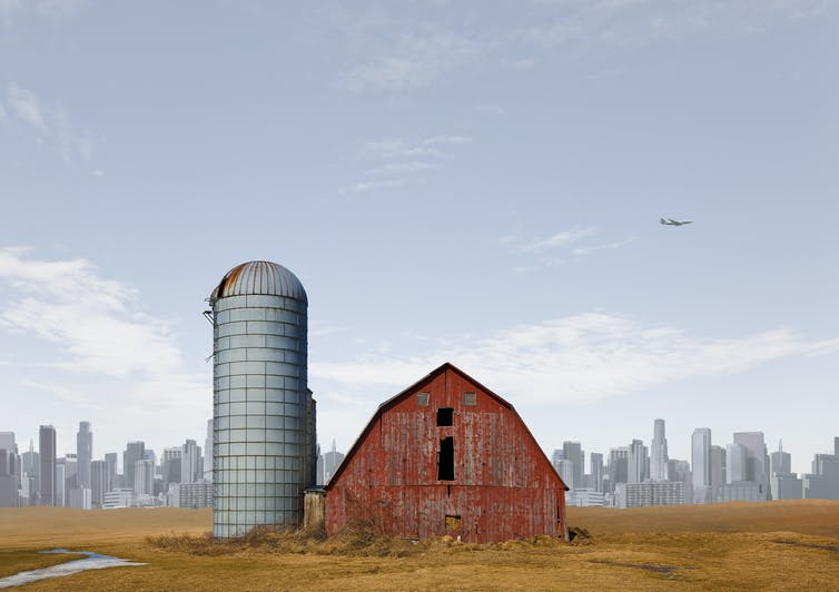 A barn in a field with a city in the background.