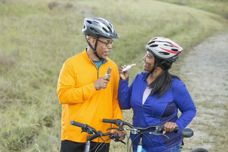 older couple eat energy bars on a bike ride