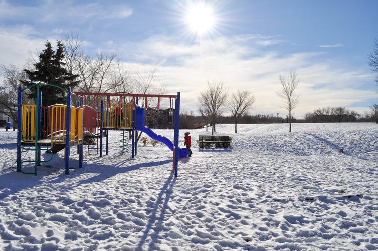 A child at a playground in winter.
