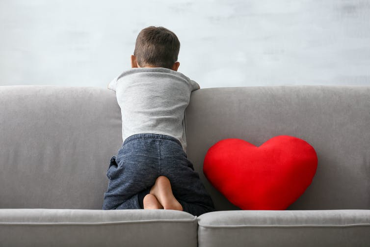 A boy faces a wall sitting on a couch.