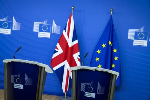 Two empty podiums in front of a Union flag and a European flag.