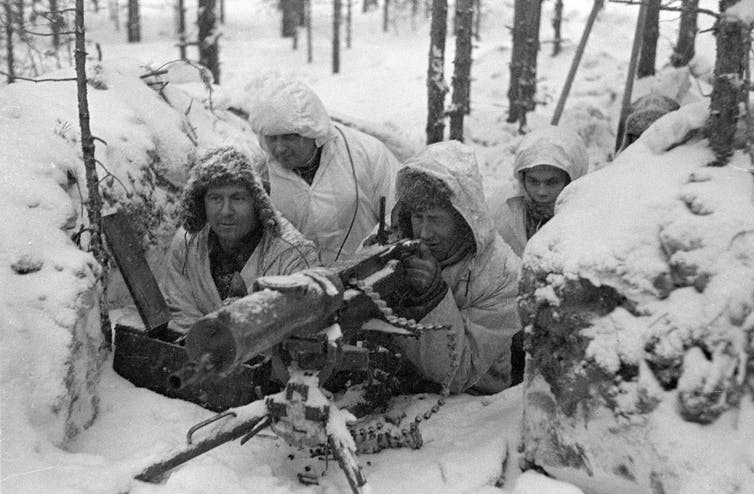 Five Finnish soldiers in winter gear man a machine gun nest surrounded by snow.