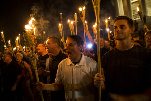 Crowd of men and women shout while holding tiki torches