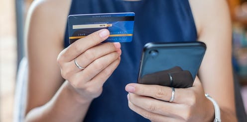 A woman holds a credit card in one hand and a smart phone in the other