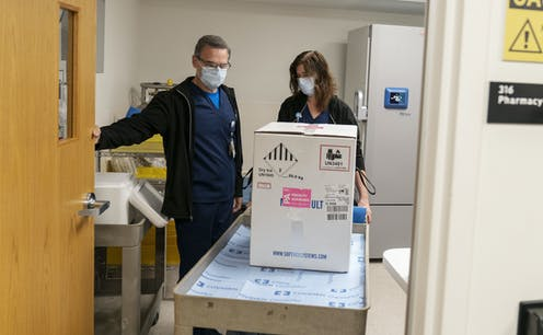 Hospital staff with a box of vaccine.