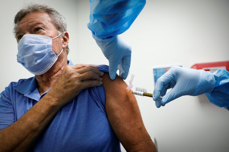 An older man receiving a COVID-19 vaccine