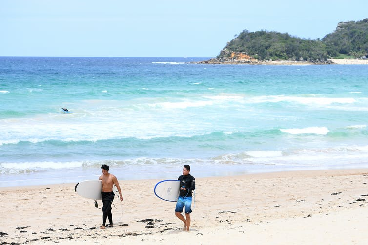Surfers walk along a Sydney beach.