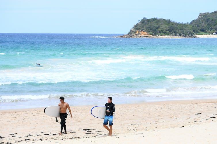 Surfers walk along a Sydney beach.