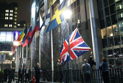 Staff removing the Union Flag from outside the European parliament.
