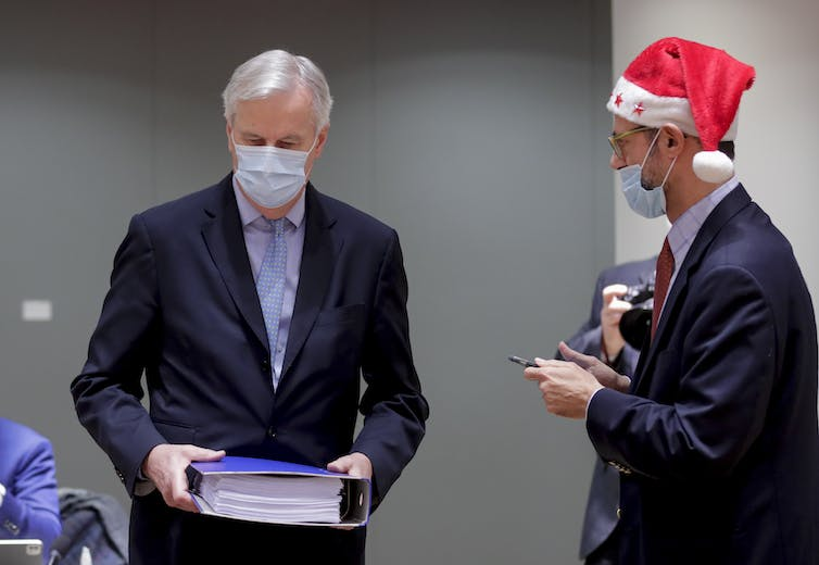 Michel Barnier holding a large binder containing the post-Brexit trade deal.