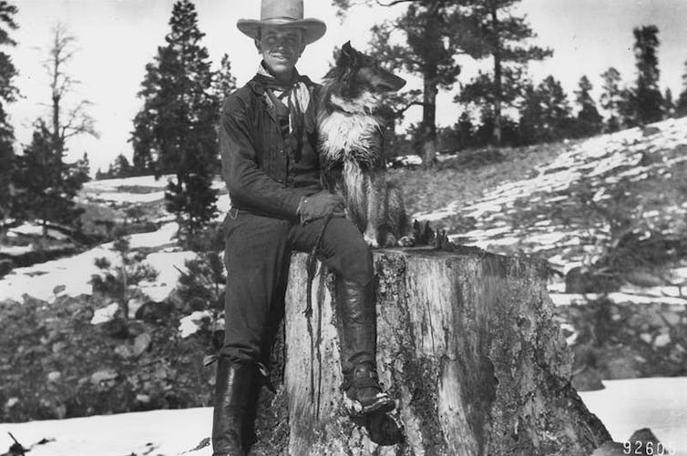 Leopold seated on large tree stump with dog