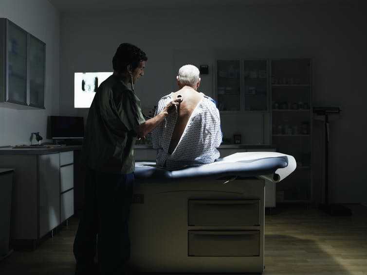A doctor examines a patient with a stethoscope.