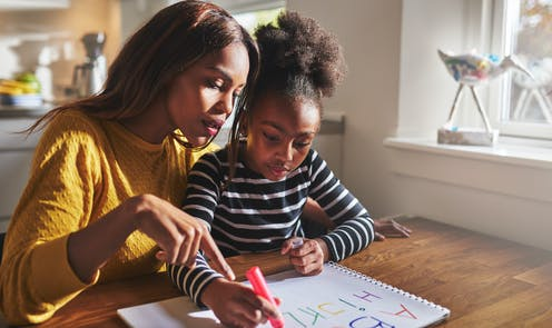 Woman in yellow jumper helping child in striped jumper with homework
