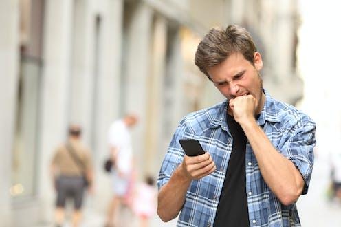 Un hombre se muerde el puño mientras mira furioso su teléfono móvil.