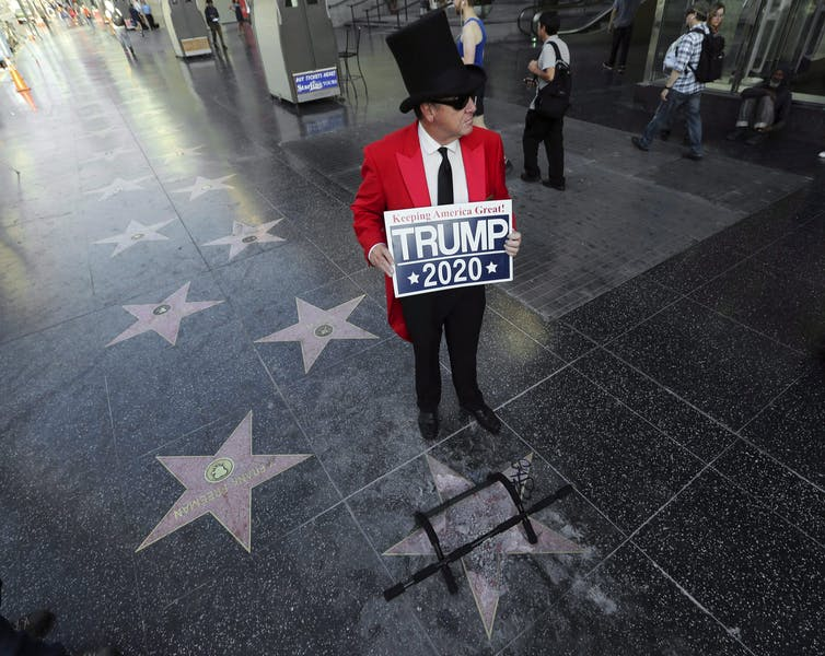 A Trump supporter carrying a Trump 2020 sign stands near the president's vandalized star on the Hollywood Walk of Fame.