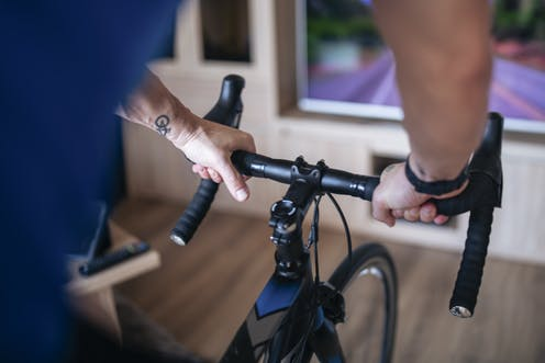 man cycling on indoor bike trainer facing screen