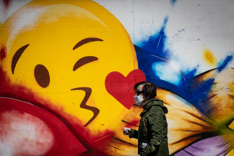 A man in a mask walks past a mural with a giant emoji.