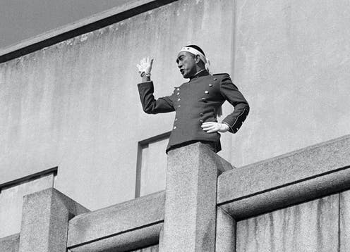 One arm akimbo and wearing a bandana, Mishima salutes the crowd with his other hand.