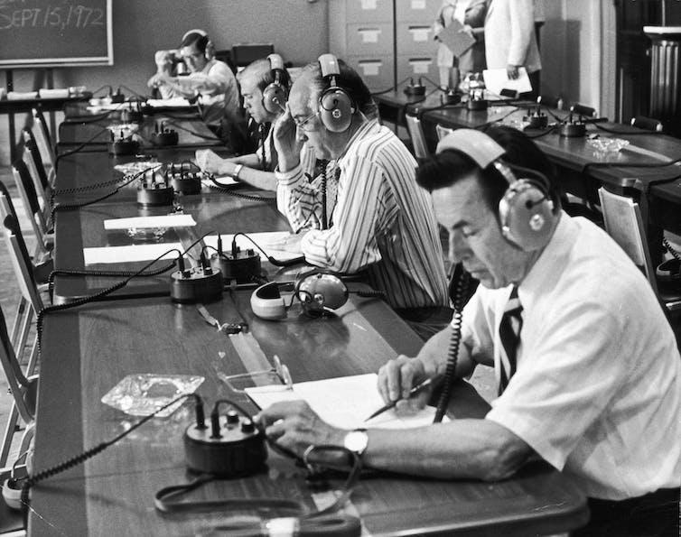 Legislators at a long table wearing headphones.