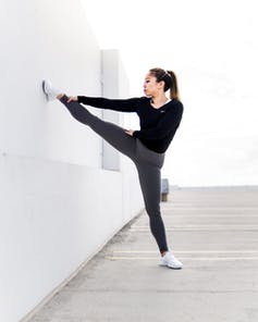 A woman in workout clothes stretching her leg