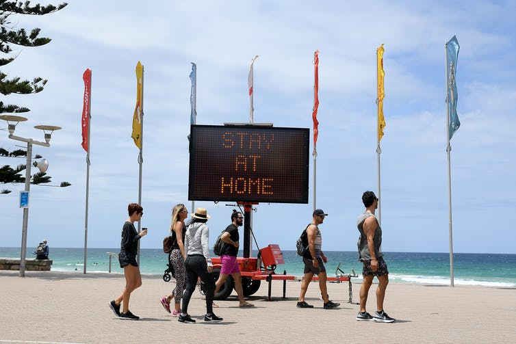 Sign on Manly Beach advising people to stay home