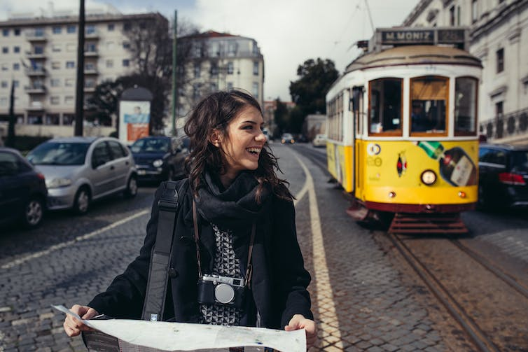 Woman with map in front of tram in city