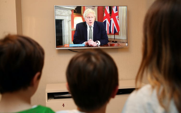 A family watches a TV screen as the prime minister announce lockdown measures.