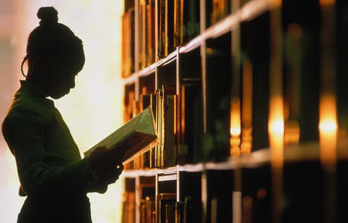 A Black woman reading in a library