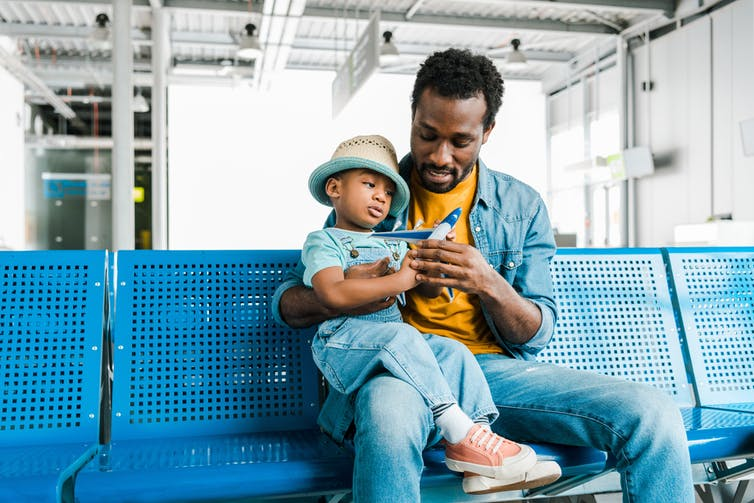 Father holds child with plane figurine on his lap at airport