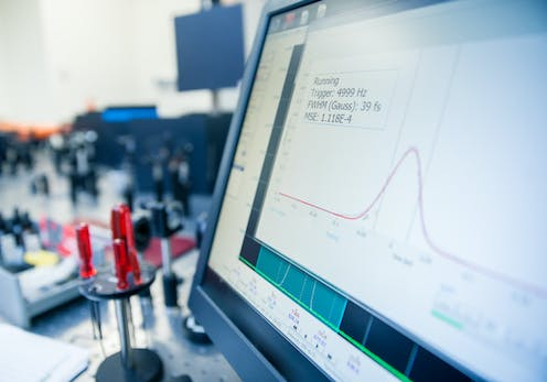 A computer monitor showing a bell curve graph with scientific instruments in the background.