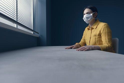 Una mujer con mascarilla en una habitación gris mira hacia la ventana luminosa tapada por una persiana.
