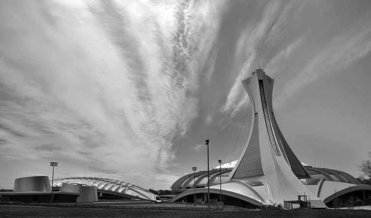 A dramatic black and white photograph of Montréal's Olympic Stadium