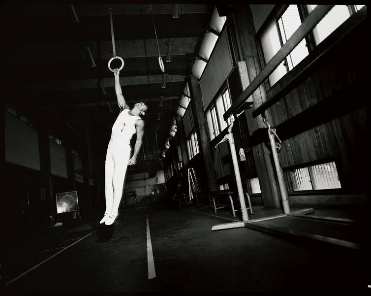 Yukio Mishima, dressed in white, hangs, bloodied, from a still ring.