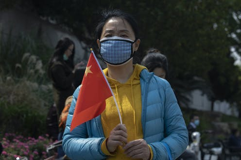 A woman outdoors wearing a mask holds a Chinese national flag
