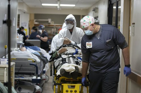 Medical staff push a gurney down a hall where another patient waits in a hospital bed.