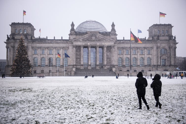 Two people walk past Berlin's Reichstag in the snow.