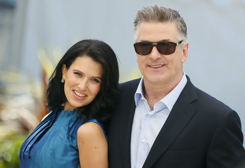 Woman with long dark hair in blue dress alongside man in lounge suit and open-necked shirt wearing sunglasses.