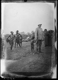 Officier colonial tenant la main d'un enfant dans un village africain, 1904-1914.