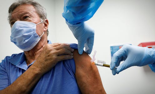 A man receiving a COVID-19 vaccine in the UK