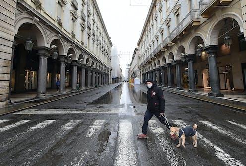 A man wearing a mask walks a dog throgh Turin.