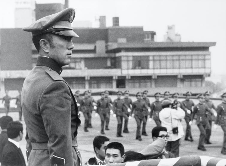 Wearing a military uniform, Mishima watches marchers.