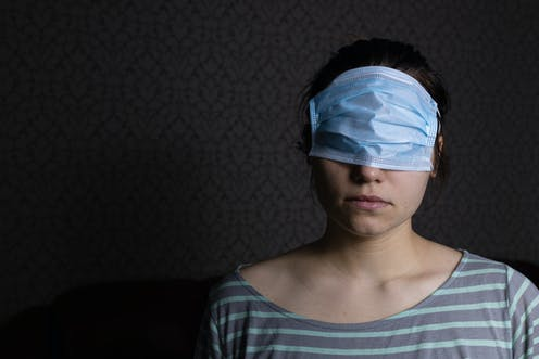 A woman wearing a surgical mask over her eyes