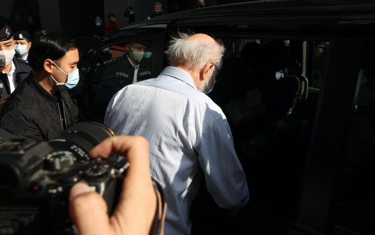 Elderly man being arrested by Chinese security forces in Hong Kong.