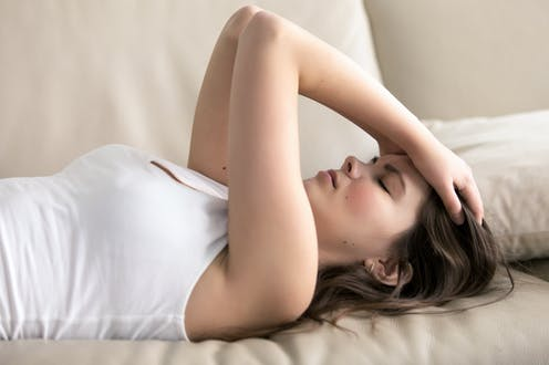 Una mujer de mediana edad tumbada con las manos en la cabeza.